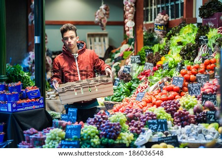 LONDON, UK - MAR 22: An unidentified man arranges fruits and vegetables in Borough Market in London on March 22, 2014.  - stock photo
