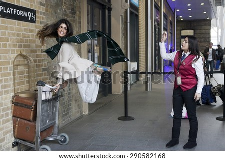 LONDON, UK - MAR 19, 2013: Kings Cross station wall visited by fans of Harry Potter to photograph sign for platform nine and three quarters with trolley - stock photo
