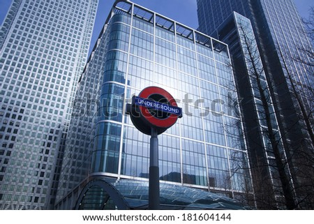 LONDON, UK - MARCH 10, 2014: Canary Wharf skyscrapers and tube station sign. Every day tube bringing about 100 000 office workers in that aria