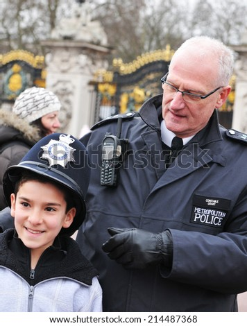 LONDON, UK - MARCH 5, 2011: London local Metropolitan policeman in uniform gives his hat to a tourist  - stock photo