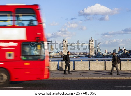 LONDON, UK - MARCH 2ND 2015: A view of a red bus and pedestrians crossing London Bridge on the 2nd March 2015.  Tower Bridge can be seen in the distance. - stock photo