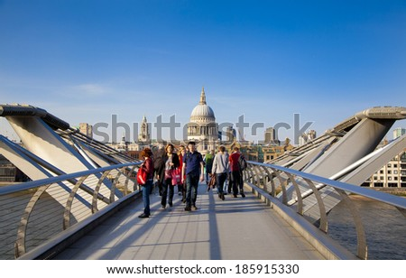 LONDON, UK - MARCH 29, 2014: South bank walk of the river Thames. View on St. Paul's cathedral from foot bridge