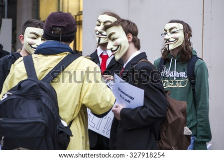 "LONDON, UK - MARCH 1TH 2014.A protester wearing a Guy Fawkes mask holds a placard ""Tax Scientology"" - stock photo"
