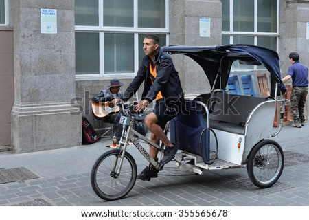 LONDON, UK - MAY 30, 2015: A man rides a rickshaw along a city centre street. Rickshaws have become a commonplace form of transport in the British capital - stock photo