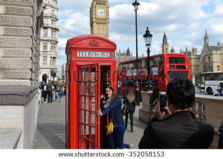 LONDON, UK - MAY 30, 2015: A tourist poses for a photo by a traditional red phonebox in Westminster. The British capital is one of the world's most visited cities with 17 million visitors in 2013.