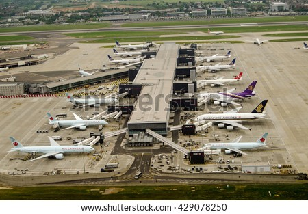 LONDON, UK - MAY 30, 2016: Aerial view of planes at Terminal 2 of London Heathrow Airport on a cloudy day. Airlines using this terminal include Air Canada, Singapore Airlines and United Airlines. - stock photo