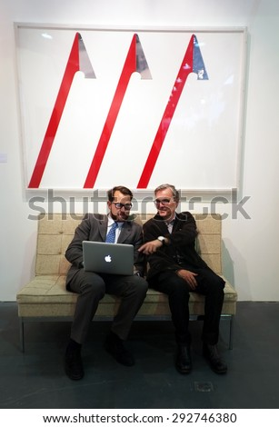 LONDON, UK - MAY 22, 2015: Gallery owners discuss business during a global art fair Art15 in London's Kensington Olympia. - stock photo