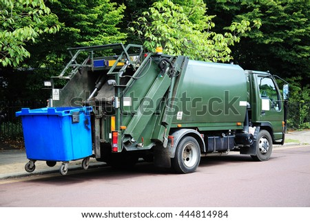 London, UK, May 30 2011 - Green garbage truck elevating a blue bin at the rear - stock photo