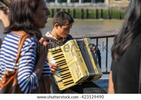 London, UK - May 10, 2015 - Immigrant busker playing accordion within crowd on London's South Bank - stock photo