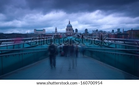 LONDON, UK - 3 MAY, Londoners walk home from St Pauls past artist on 3 May 2013. The dome at 365 feet high towers over Millenium Bridge