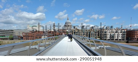 LONDON, UK - MAY 12 2015:Pedestrian cross over the Millennium Bridge in London, UK. It is London first dedicated pedestrian footbridge - stock photo