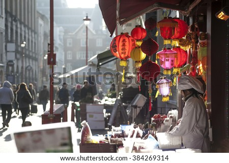 LONDON, UK - MAY 30, 2015: People walk along a busy shopping street in London's Chinatown. Over 120,000 people of Chinese ethnicity live in the British capital, 33% of the UK's Chinese population. - stock photo