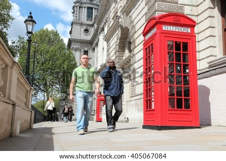 LONDON, UK - MAY 16, 2012: People walk by red telephone booth in London. With more than 14 million international arrivals in 2009, London is the most visited city in the world (Euromonitor). - stock photo