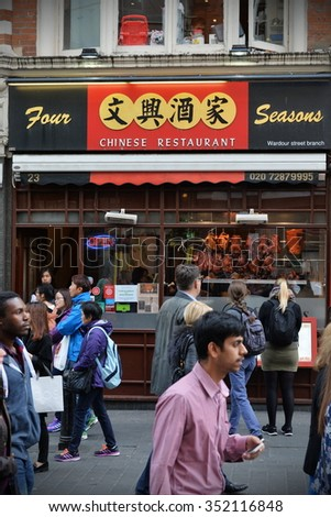LONDON, UK - MAY 30, 2015: People walk past a Chinese restaurant on a street in Chinatown. Over 120,000 people of Chinese ethnicity live in the British capital, 33% of the UK's Chinese population.