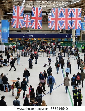 LONDON, UK - MAY 30, 2015: Rail travelers walk through Victoria Train Station. Victoria is the second busiest train station in the British capital with 73 million passengers entry and exits yearly. - stock photo