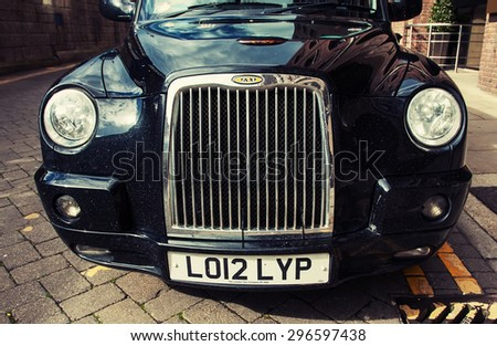 London, UK - May 7, 2014: Taxi in the street in London, UK. Cabs, Taxis, are the most iconic symbol of London as well as London's Red Double Decker Bus  - stock photo