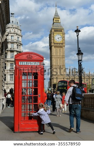 LONDON, UK - MAY 30, 2015: Tourists view a traditional red British phone box at Westminster near Big Ben and the Houses of Parliament. London had 17 million international visitors in 2013. - stock photo