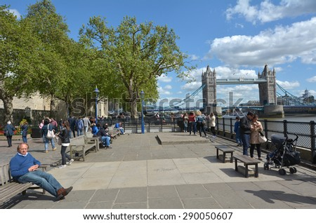 LONDON, UK - MAY 12 2015:Visitors and The Tower Bridge spanning over River Thames as view from London borough of Tower Hamlets (north side) in London, UK.