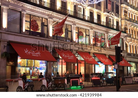 London, UK - November 12, 2011: Hamleys toy department store in Regent Street at night, with  rickshaw vehicles waiting outside for customers during the Christmas festival season - stock photo