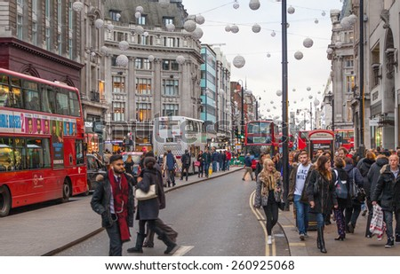 LONDON, UK - NOVEMBER 30, 2014: Regent street, Oxford circus with lots of pedestrians and cars, taxis on the road.  - stock photo