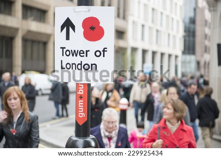 LONDON, UK - NOVEMBER 08: Street sign with red poppy pointing to the Tower of London. November 08, 2014 in London. The ceramic poppies installation was created to mark the centenary of WWI's outbreak. - stock photo