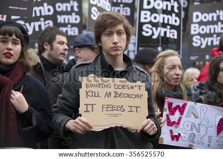 LONDON, UK - NOVEMBER 28, 2015 Unidentified protesters holding protest banners during a protest against UK bombing Syria outside Downing Street in Whitehall.