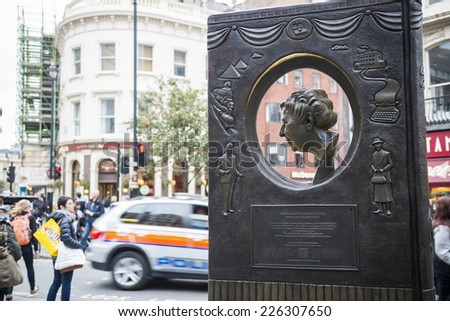 LONDON, UK - OCTOBER 26: Agatha Christie book shaped memorial with busy street in the background. The bronze memorial was unveiled on the 18 November 2012. October 26, 2014 in London. - stock photo