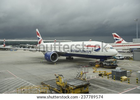 London, UK - October 31, 2013: British Airways passenger planes stand at their gates under dark skies at Heathrow Airport. - stock photo
