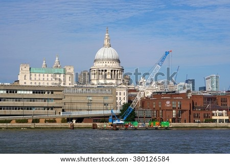 LONDON, UK - OCTOBER 11 2015: Pedestrians walk along the north bank of the River Thames in London, England near St Paul's Cathedral and the City of London, where a crane is operating on a river barge.