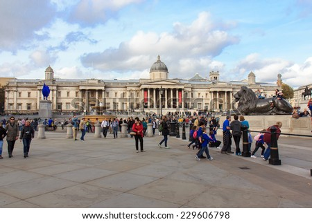 LONDON, UK - OCTOBER 17, 2014: Tourists visit Trafalgar Square October 17, 2014 in London. One of the most popular tourist attraction on Earth it has more than fifteen million visitors a year.