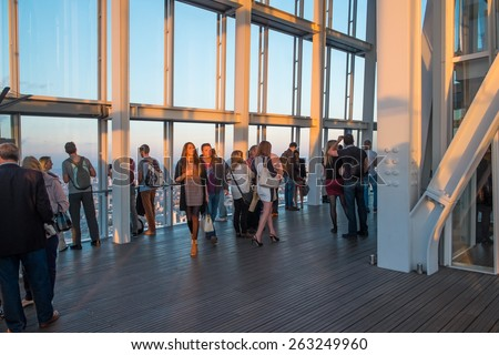 LONDON, UK - OCTOBER 3, 2014: Visitors on the viewing platform in The Shard, the tallest building in London at sunset in October 2014. - stock photo