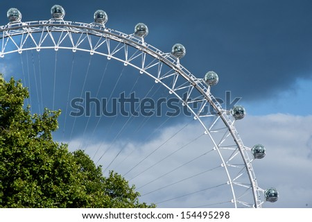LONDON, UK - SEP 16: the London Eye against a dramatic cloudy sky in London on September 16, 2013. The structure is 135 meters tall and the wheel has a diameter of 120 metres. - stock photo