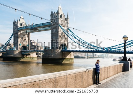 LONDON, UK - SEPTEMBER 28, 2014: A young boy is taking a selfie in front of the Tower Bridge on September 28, 2014 in London, UK. - stock photo