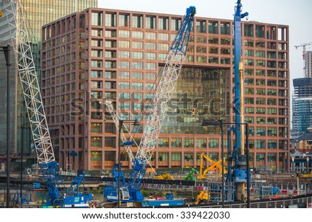 LONDON, UK - SEPTEMBER 9, 2015: Building construction site with cranes and industrial units  in Canary Wharf aria  - stock photo