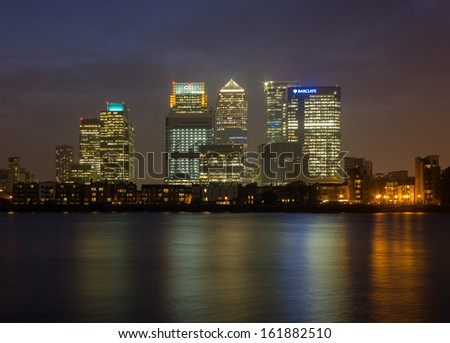 LONDON, UK - SEPTEMBER 24, 2013: Canary Wharf at night from across the Thames showing some financial buildings and offices litup against the night sky on September 24th 2013 - stock photo