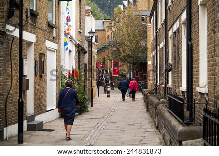 LONDON, UK - SEPTEMBER 7TH, 2014: people walking (and cycling) a narrow street in Greenwich, London