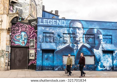 London, UK - 19 September 2015: Two middle aged men walking in front of street graffiti promoting the release of the movie Kray's Legend. Shot in Shoreditch an area of London famous for street art. - stock photo