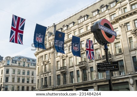 LONDON, UK - SEPTEMBER 27: Union Jack and NFL banners with London Underground sign post. September 27, 2014 in London. Regent street was closed to traffic to host NFL related games and events. - stock photo