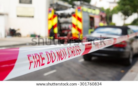 London, UK - 31st July 2015 - Fire Do Not Cross tape with fire engine in background - stock photo