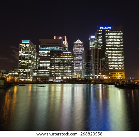 LONDON, UK - 26TH MARCH 2015:  A view of Canary Wharf at night showing buildings and reflections in the water - stock photo