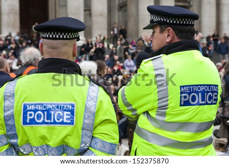 LONDON, UK - 30TH OCTOBER 2011: Two Police officers overseeing the Occupy London protest camp outside St. Paul's Cathedral in London on 30th October 2011. - stock photo