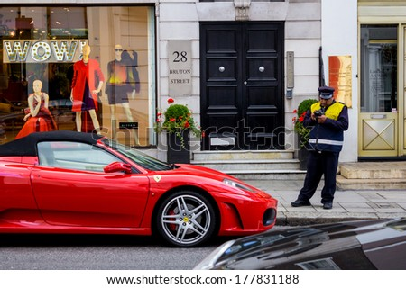 LONDON, UK - 7TH SEPTEMBER 2013: A parking attendant writing a ticket for a Ferrari - stock photo
