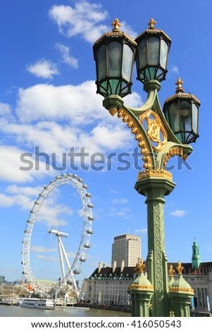 LONDON, UNITED KINGDOM - APRIL 19, 2016: Iconic London's lamp post and London Eye at the background