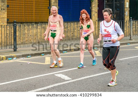 """London, United Kingdom - April 24, 2016: London Marathon 2016. Runners in great costumes. Adam and Eve costume - """"naked effect"""" costumes with fig leaves - stock photo"""