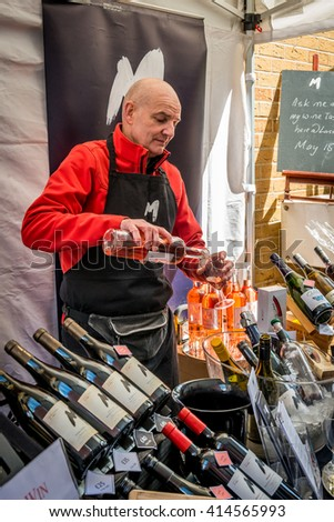 London, United Kingdom - April 30, 2016: Maltby Street Market in Bermondsey (located in railway arches, SE1, Rope Walk). Great artisan street food stalls and bars. Wine vendor is pouring rose wine