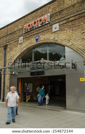 LONDON, UNITED KINGDOM - AUGUST 28, 2014:  Passengers using the main entrance to Hoxton Railway Station, part of London Transport's Overground network in fashionable East London. - stock photo