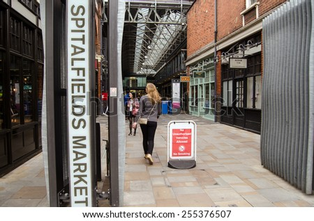 LONDON, UNITED KINGDOM - AUGUST 30, 2014:  Shoppers at the entrance to the trendy Spitalfields Market in Shoreditch, London.  The covered market is famous for fashion and is popular with hipsters.