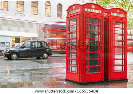 LONDON, UNITED KINGDOM - CIRCA NOVEMBER 2013:Red Phone cabines in London and vintage taxi.Rainy day. Vintage phone cabine monumental - stock photo