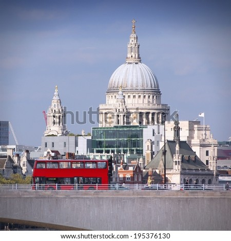 London, United Kingdom - cityscape with famous St. Paul's Cathedral and a bridge with red doubledecker bus. Square composition. - stock photo