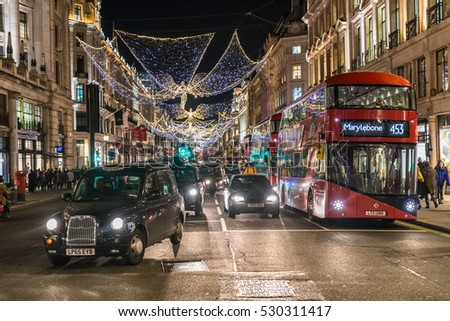 LONDON, UNITED KINGDOM - DECEMBER 1, 2016: Busy Regent's street, taxi and red double decker bus at night with Christmas decorations above the street.